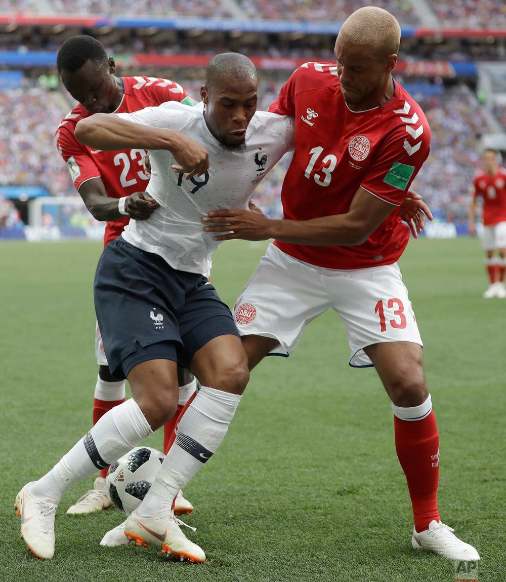 France's Djibril Sidibe, centre is tackled by Denmark's Pione Sisto, left, and Denmark's Mathias Jorgensen during the group C match between Denmark and France at the 2018 soccer World Cup at the Luzhniki Stadium in Moscow, Russia, Tuesday, June 26, 2018. (AP Photo/Matthias Schrader)