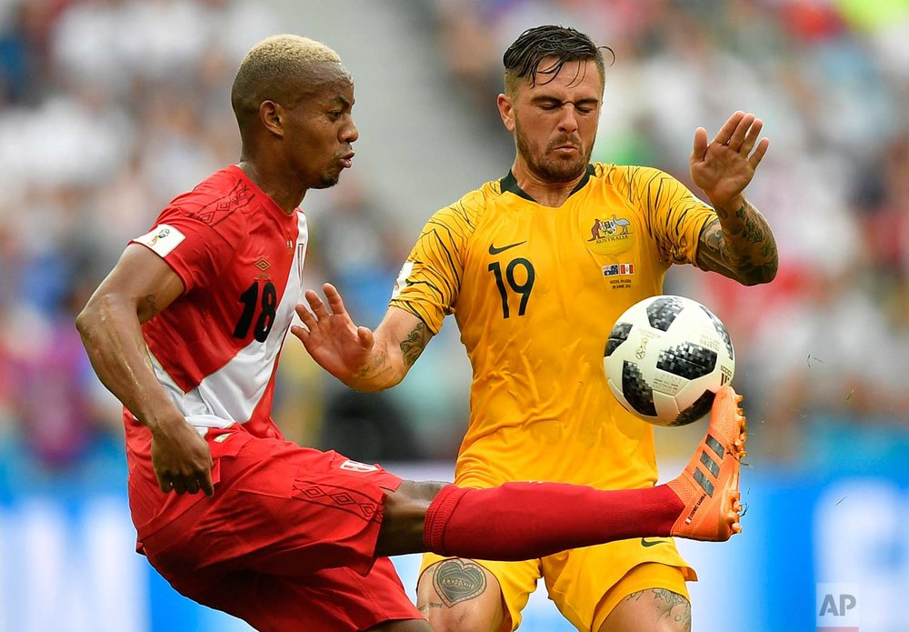 Peru's Andre Carrillo, left, and Australia's Joshua Risdon challenge for the ball during the group C match between Australia and Peru, at the 2018 soccer World Cup in the Fisht Stadium in Sochi, Russia, Tuesday, June 26, 2018. (AP Photo/Martin Meissner)