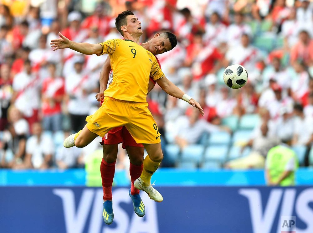 Peru's Anderson Santamaria, background, and Australia's Tomi Juric go for a header during the group C match between Australia and Peru, at the 2018 soccer World Cup in the Fisht Stadium in Sochi, Russia, Tuesday, June 26, 2018. (AP Photo/Martin Meissner)