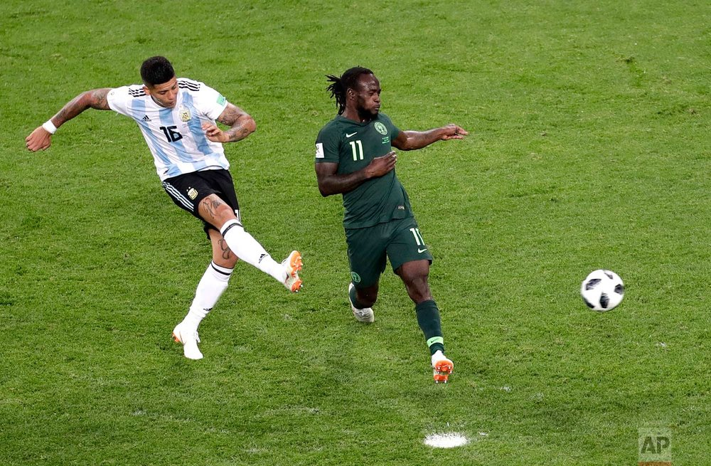 Argentina's Marcos Rojo, left, scores his side's second goal past Nigeria's Victor Moses during the group D match between Argentina and Nigeria, at the 2018 soccer World Cup in the St. Petersburg Stadium in St. Petersburg, Russia, Tuesday, June 26, 2018. (AP Photo/Michael Sohn)