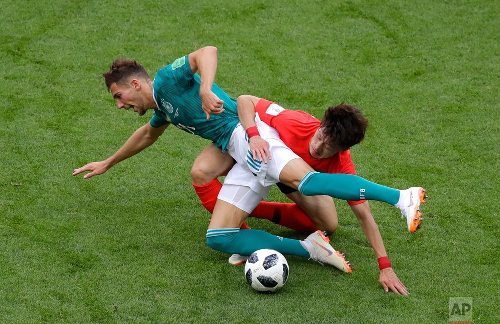 Germany's Leon Goretzka fights for the ball with South Korea'sLeeJae-sung, right, during the group F match between South Korea and Germany, at the 2018 soccer World Cup in the Kazan Arena in Kazan, Russia, Wednesday, June 27, 2018. (AP Photo/Sergei Grits)