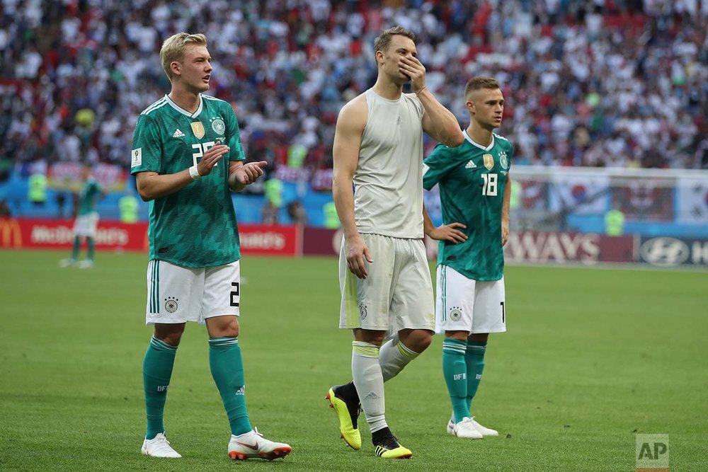 From left, Germany's Julian Brandt goalkeeper Manuel Neuer and Joshua Kimmich walk on the pitch at the end of the group F match between South Korea and Germany, at the 2018 soccer World Cup in the Kazan Arena in Kazan, Russia, Wednesday, June 27, 2018. South Korea won 2-0. (AP Photo/Thanassis Stavrakis)