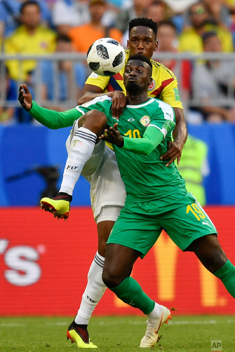 Senegal's Mbaye Niang, bottom, vies for the ball with Colombia's Oscar Murillo, top, during the group H match between Senegal and Colombia, at the 2018 soccer World Cup in the Samara Arena in Samara, Russia, Thursday, June 28, 2018. (AP Photo/Martin Meissner)