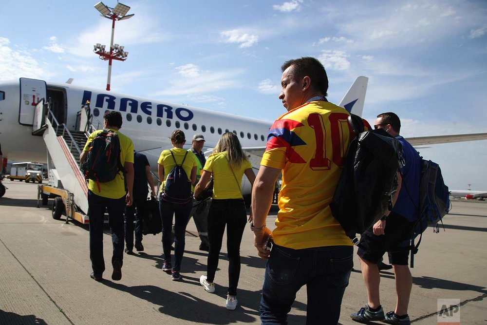 In this Sunday, June 24, 2018 photo, Colombian fans embark a plane at the Vnukovo International Airport in Moscow, Russia.  (AP Photo/Thanassis Stavrakis)