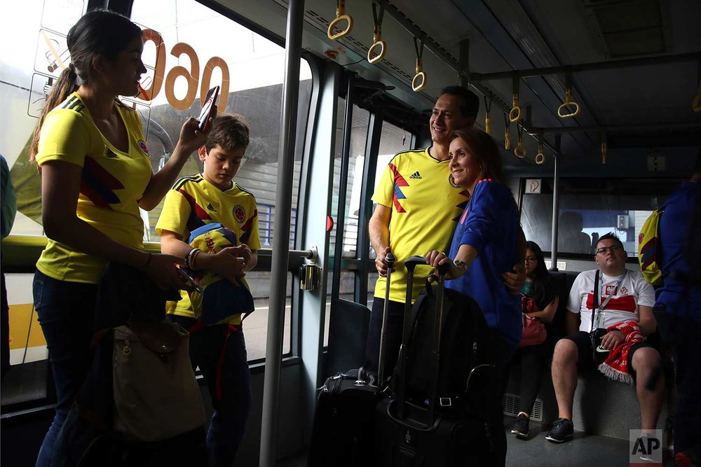 In this Sunday, June 24, 2018 photo, a family from Colombia take photos as a Polish fan sits in a shuttle bus at Vnukovo International Airport in Moscow, Russia.  (AP Photo/Thanassis Stavrakis)