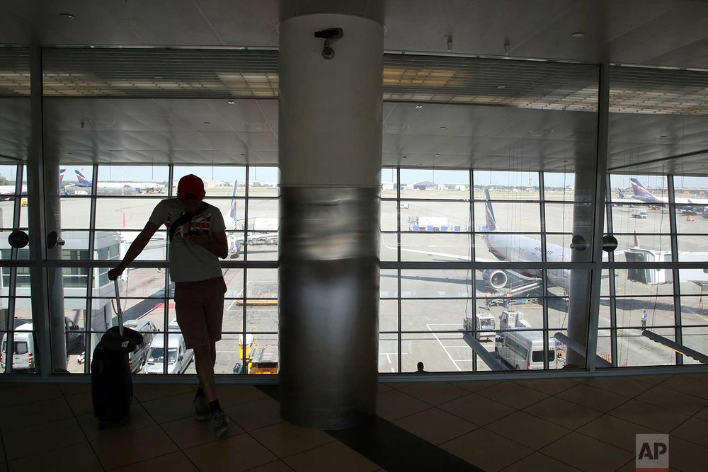 In this Friday, June 22, 2018 photo, a soccer fan wearing a T-shirt with the British flag checks his cellphone after a flight at Sheremetyevo International Airport, in Moscow, Russia.  (AP Photo/Thanassis Stavrakis)