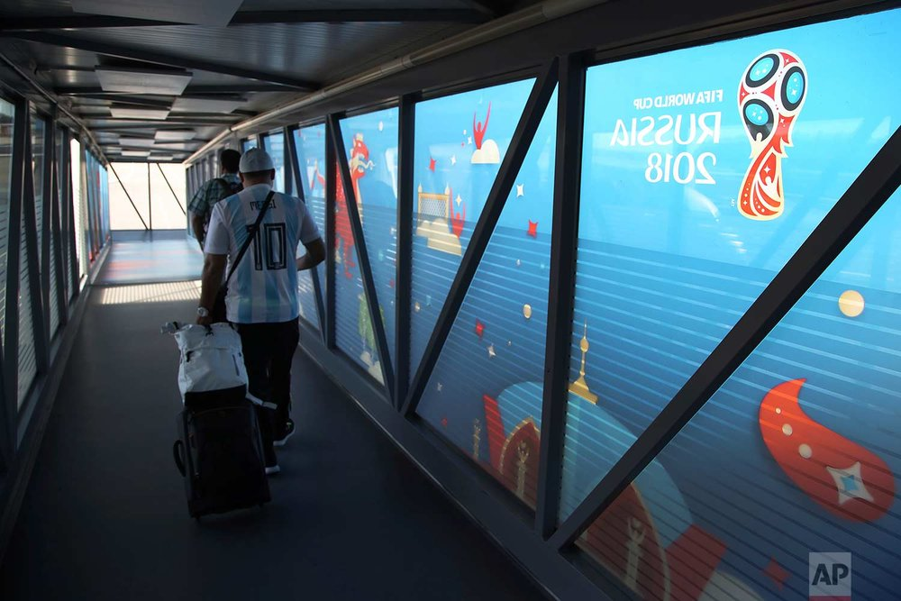 In this Friday, June 22, 2018 photo, a supporter of Argentina embarks a plane at Kazan International Airport in Kazan, Russia.  (AP Photo/Thanassis Stavrakis)