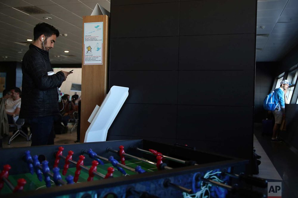 In this Friday, June 22, 2018 photo, a passenger checks his cellphone next to a table soccer as other fans wait to embark a plane at Kazan International Airport in Kazan, Russia.  (AP Photo/Thanassis Stavrakis)