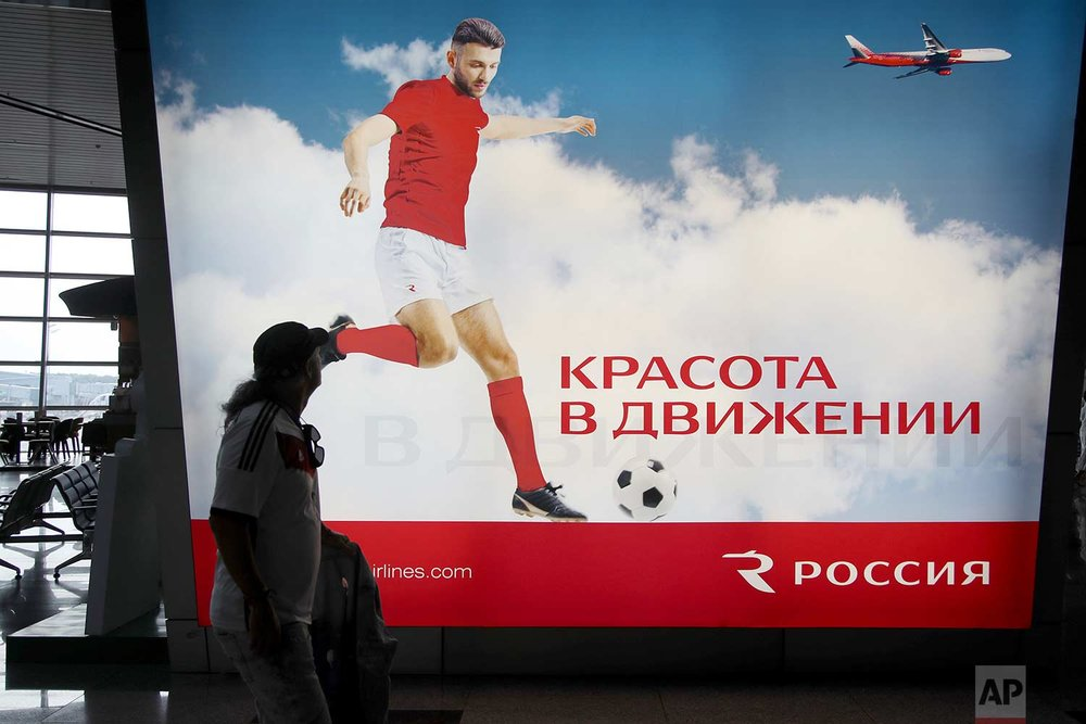 In this Sunday, June 24, 2018 photo, a supporter of Germany looks at an advertising banner that reads in Russian language ''Beauty in motion'' at Vnukovo International Airport in Moscow, Russia. (AP Photo/Thanassis Stavrakis)