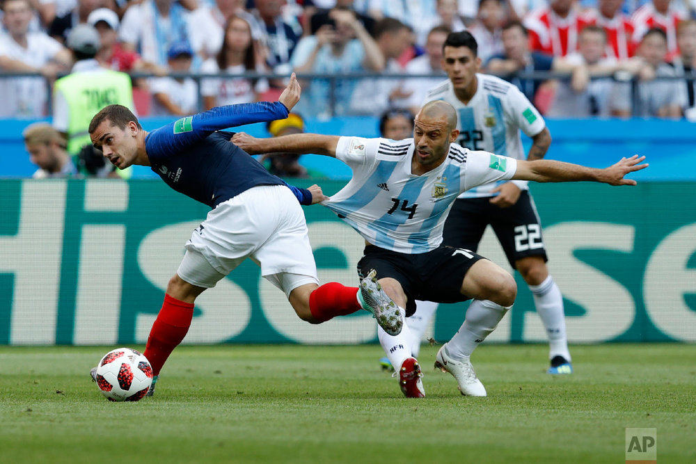 France's Antoine Griezmann, left, and Argentina's Javier Mascherano challenge for the ball during the round of 16 match between France and Argentina, at the 2018 soccer World Cup at the Kazan Arena in Kazan, Russia, Saturday, June 30, 2018. (AP Photo/David Vincent)