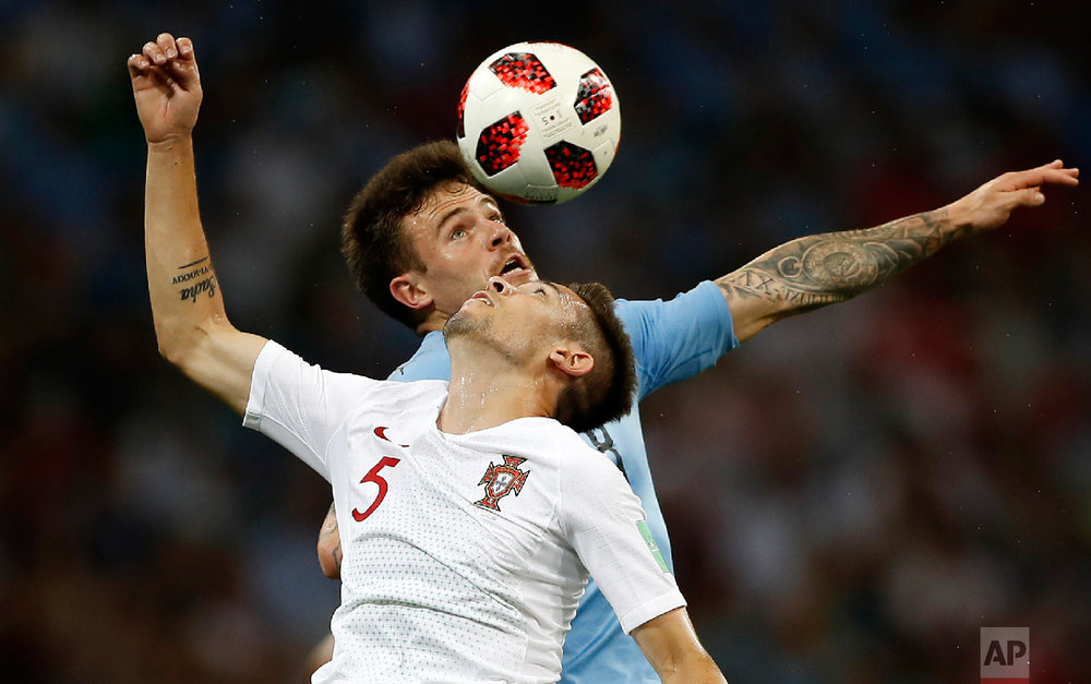 Portugal's Raphael Guerreiro and Uruguay's Nahitan Nandez, top, challenge for the ball during the round of 16 match between Uruguay and Portugal at the 2018 soccer World Cup at the Fisht Stadium in Sochi, Russia, Saturday, June 30, 2018. (AP Photo/Francisco Seco)