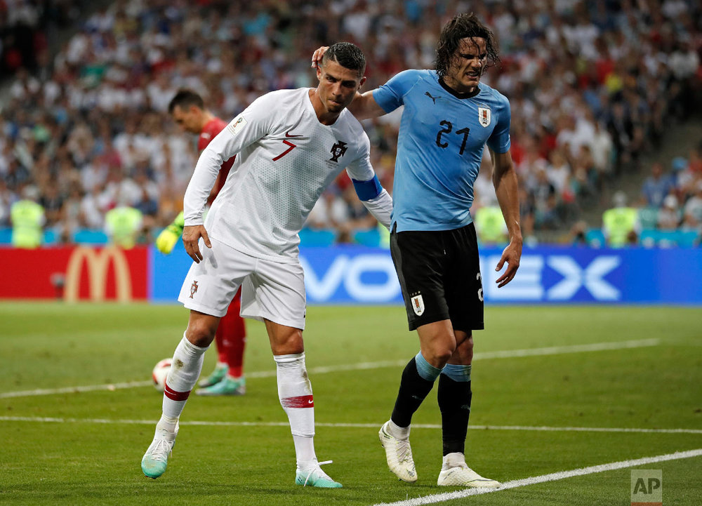 Portugal's Cristiano Ronaldo helps injured Uruguay's Edinson Cavani walking out during the round of 16 match between Uruguay and Portugal at the 2018 soccer World Cup at the Fisht Stadium in Sochi, Russia, Saturday, June 30, 2018. (AP Photo/Francisco Seco)