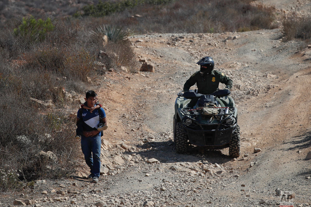 A Guatemalan father and son, who crossed the U.S.-Mexico border illegally, are escorted down a hill by a U.S. Border Patrol agent June 28, 2018, in San Diego. (AP Photo/Jae C. Hong)