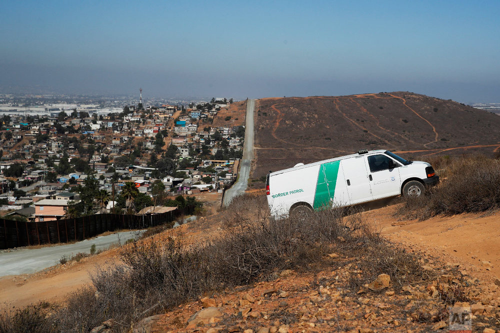 A U.S. Border Patrol van drives up the hill to pick up migrants apprehended trying to cross the U.S.-Mexico border illegally as the Mexican land looks on the left side of the border wall along a road Thursday, June 28, 2018, in San Diego. (AP Photo/Jae C. Hong)