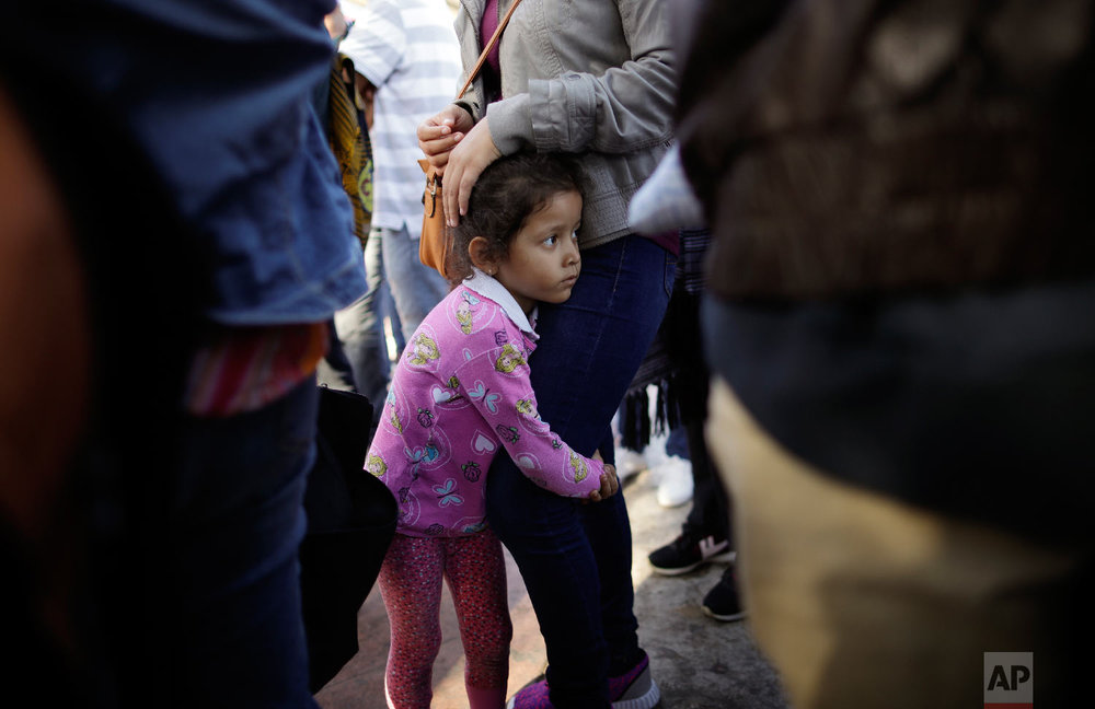 Nicole Hernandez, of the Mexican state of Guerrero, holds on to her mother as they wait with other families to request political asylum in the United States, across the border in Tijuana, Mexico on June 13, 2018. The family has waited for about a week in this Mexican border city, hoping for a chance to escape widespread violence in their home state. (AP Photo/Gregory Bull)