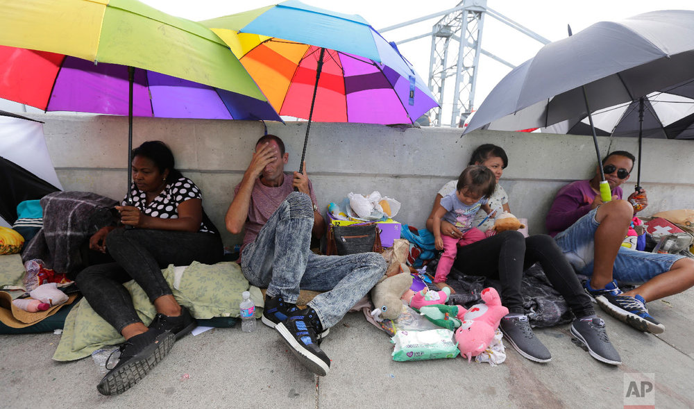 Immigrants from Guatemala and Cuba seeking asylum in the United States wait on the Matamoros International Bridge, Thursday, June 28, 2018, in Matamoros, Mexico. (AP Photo/Eric Gay)