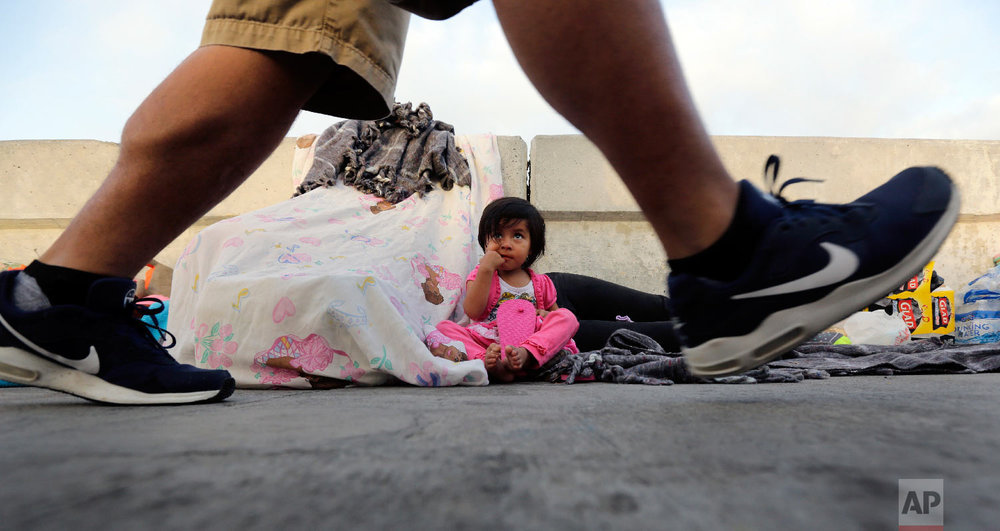 A pedestrian on the Matamoros International Bridge passes Jennifer, 2, from Guatemala seeking asylum in the United States with her mother, Friday, June 29, 2018, in Matamoros, Mexico. (AP Photo/Eric Gay)