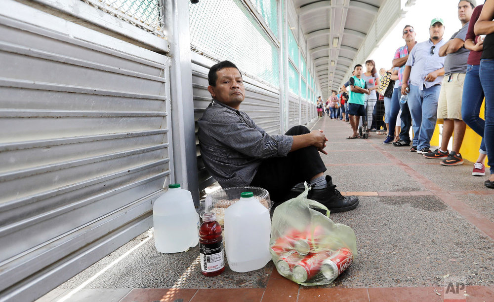 Ruben Prado, an immigrant from Guatemala seeking asylum in the United States, waits on the Gateway International Bridge in Matamoros, Mexico on Sunday, June 24, 2018. Prado arrived at the bridge today after traveling for 20 days. (AP Photo/David J. Phillip)