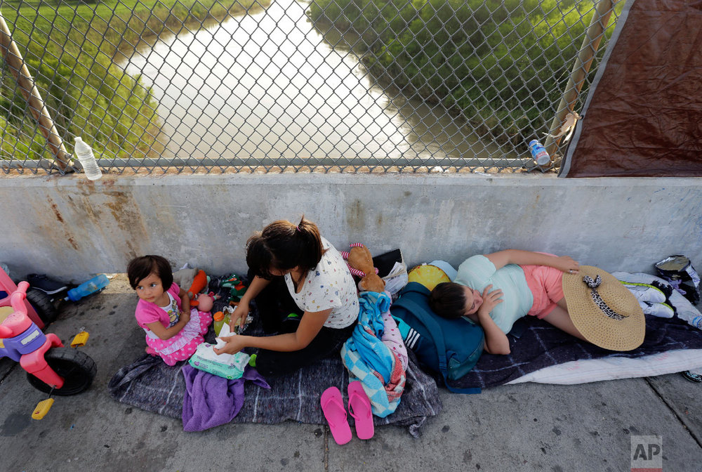 Immigrants from Cuba and Guatemala seeking asylum in the United States wait on the Matamoros International Bridge above the Rio Grande, Friday, June 29, 2018, in Matamoros, Mexico. (AP Photo/Eric Gay)