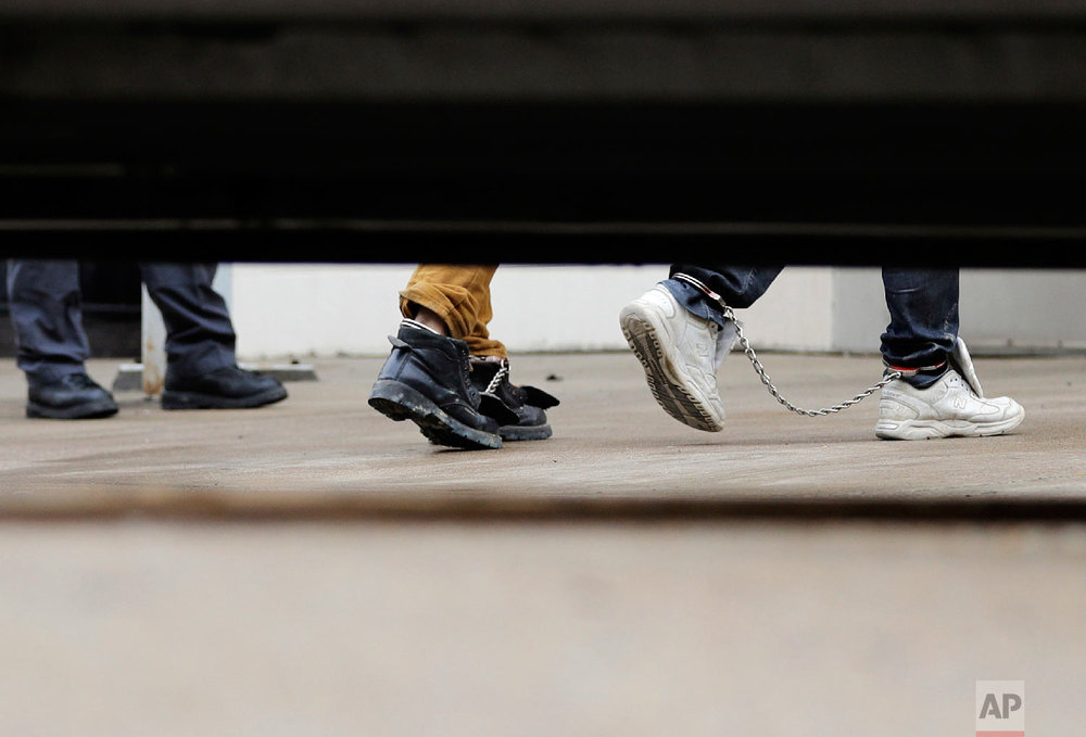 Immigrants in ankle chains disembark from a bus at the Federal Courthouse for hearings on Friday, June 22, 2018, in McAllen, Texas. (AP Photo/David J. Phillip)