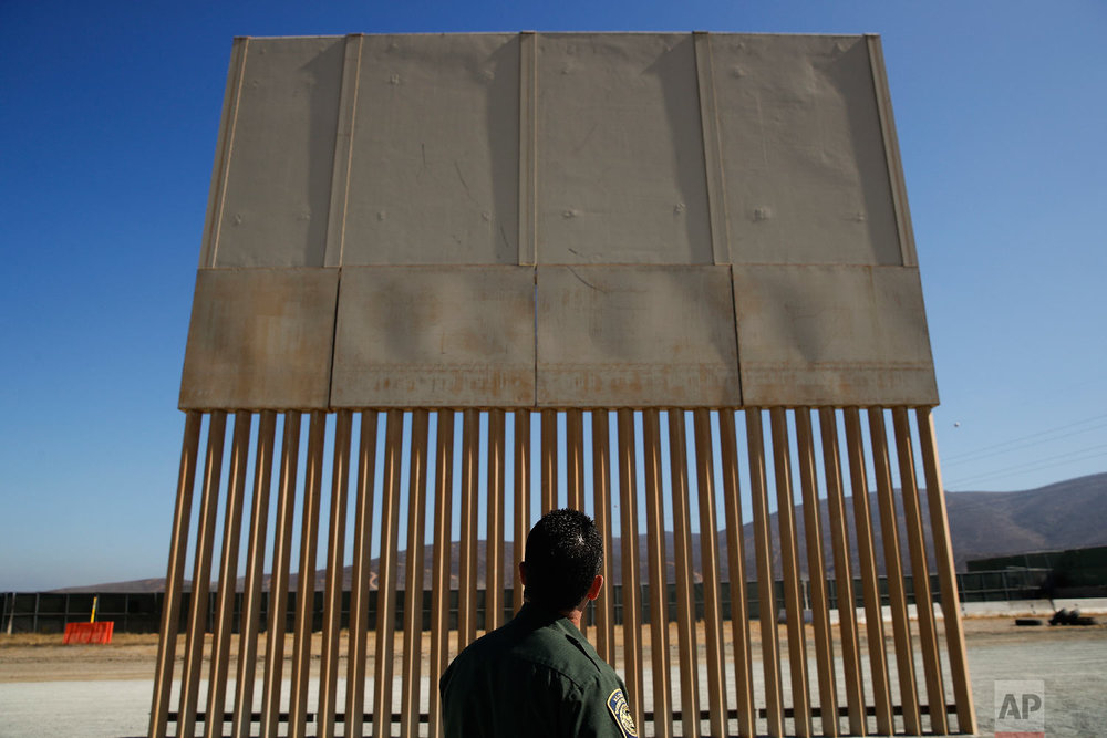 A U.S. Border Patrol agent looks at one of border wall prototypes Thursday, June 28, 2018, in San Diego. (AP Photo/Jae C. Hong)