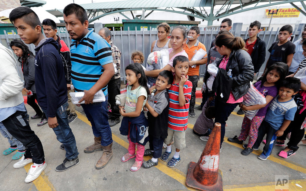 Immigrant families line up to enter the central bus station after they were processed and released by U.S. Customs and Border Protection, Sunday, June 24, 2018, in McAllen, Texas. (AP Photo/David J. Phillip)