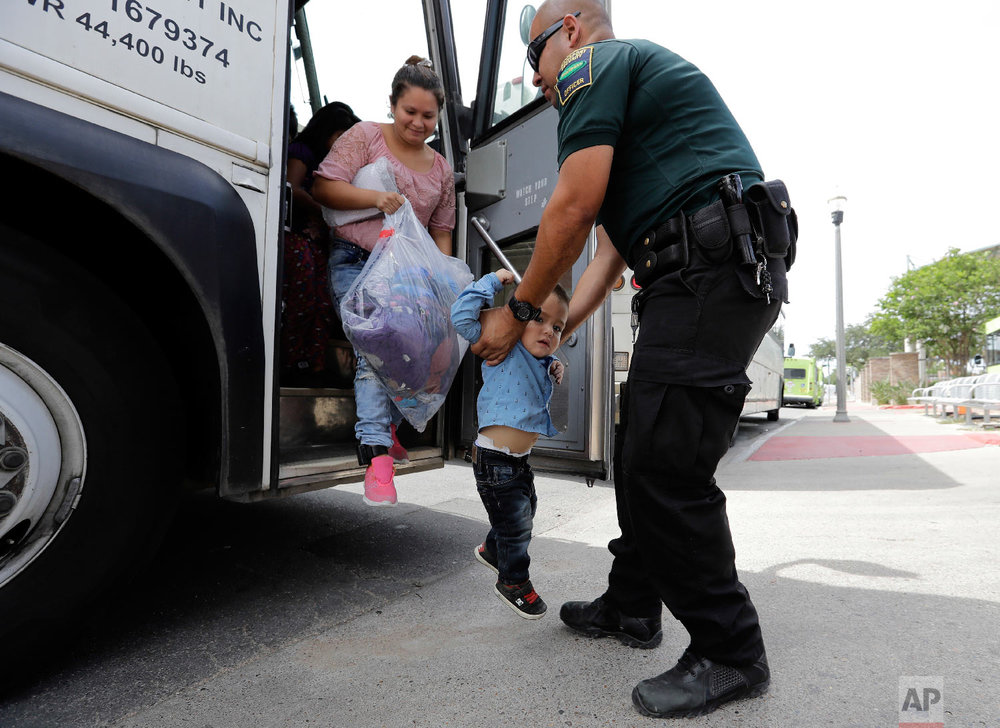 A transport officer, right, helps immigrants Dilma Araceley Riveria Hernandez, and her son, Anderson Alvarado, 2, get off the bus after they were processed and released by U.S. Customs and Border Protection, Sunday, June 24, 2018, in McAllen, Texas. (AP Photo/David J. Phillip)