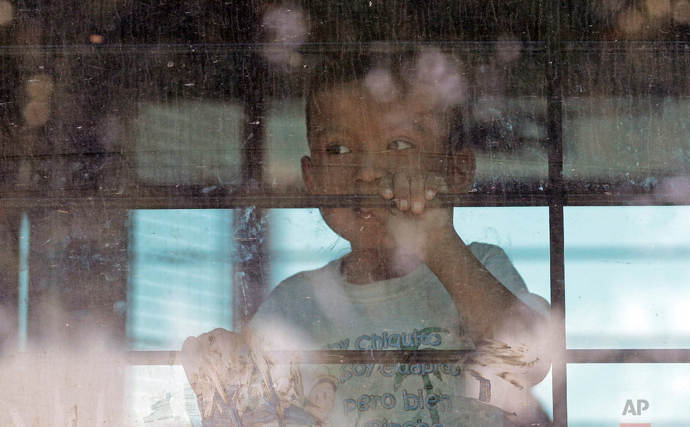 An immigrant child looks out from a U.S. Border Patrol bus leaving as protesters block the street outside the U.S. Border Patrol Central Processing Center on Saturday, June 23, 2018, in McAllen, Texas. (AP Photo/David J. Phillip)