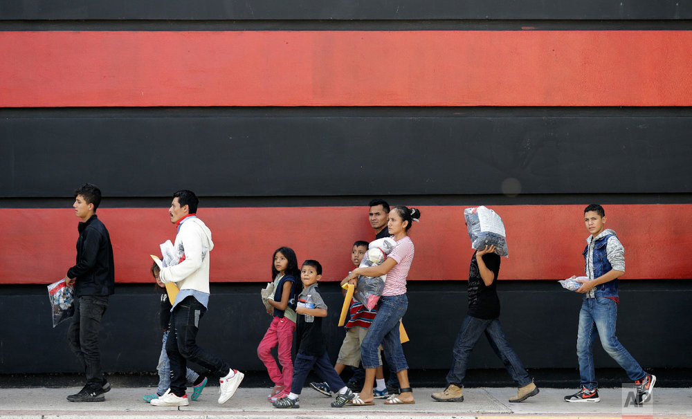 Immigrant families walk along a sidewalk on their way to a respite center after they were processed and released by U.S. Customs and Border Protection, Sunday, June 24, 2018, in McAllen, Texas. (AP Photo/David J. Phillip)