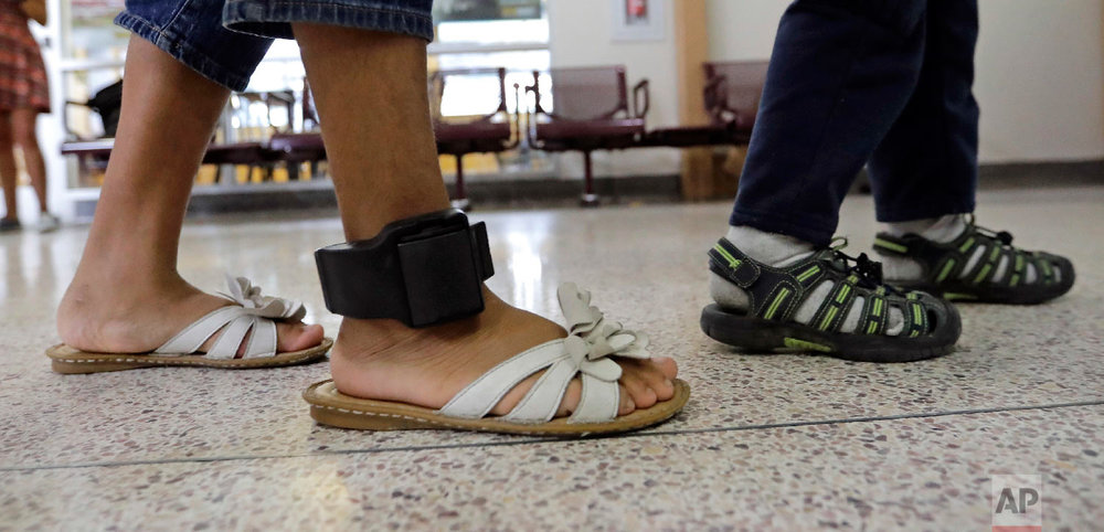 An immigrant woman wears an ankle monitor as she walks through the central bus station after being processed and released by U.S. Customs and Border Protection, Sunday, June 24, 2018, in McAllen, Texas. (AP Photo/David J. Phillip)