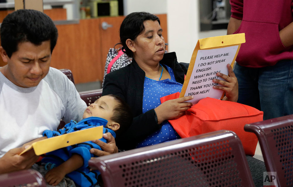 Immigrants from Guatemala seeking asylum look over travel packets as they wait at the bus station after they were processed and released by U.S. Customs and Border Protection, Thursday, June 21, 2018, in McAllen, Texas. (AP Photo/Eric Gay)