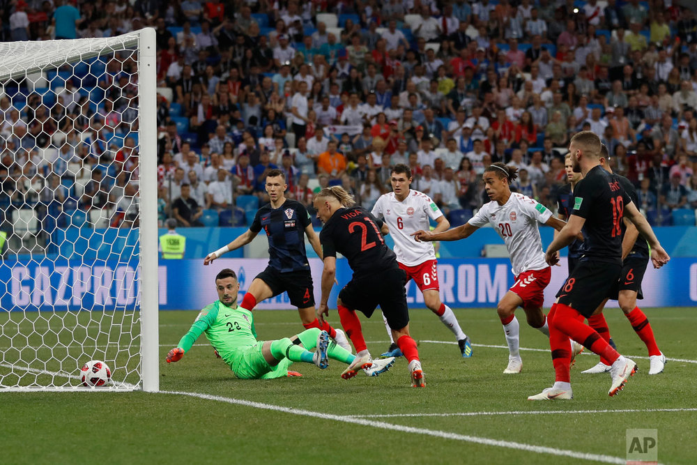 Croatia goalkeeper Danijel Subasic, left on the pitch, looks at the ball after Denmark's Mathias Jorgensen scored the opening goal during the round of 16 match between Croatia and Denmark at the 2018 soccer World Cup in the Nizhny Novgorod Stadium, in Nizhny Novgorod , Russia, Sunday, July 1, 2018. (AP Photo/Darko Bandic)