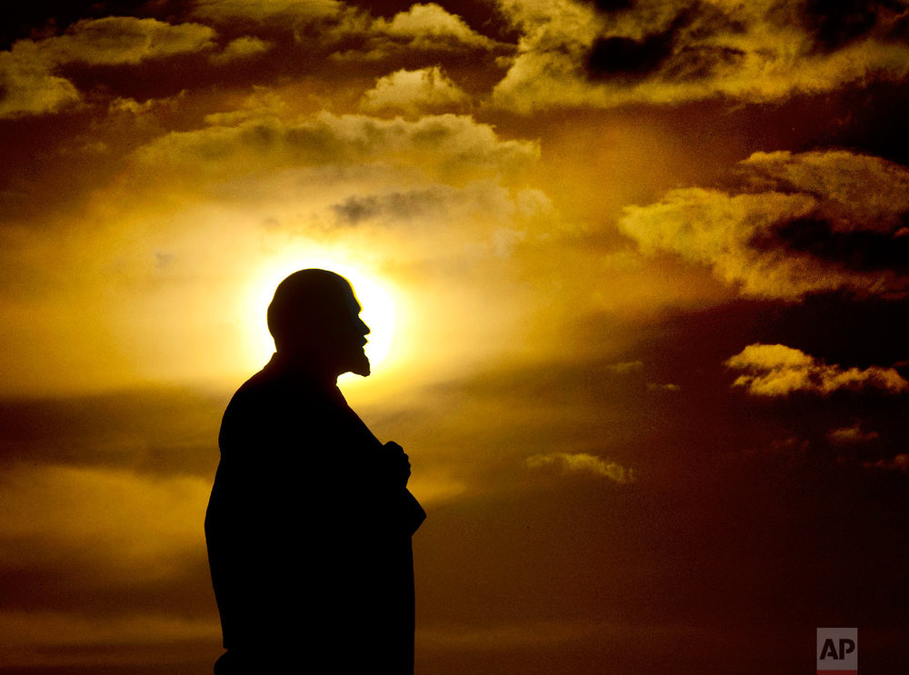 The sun sets behind a Lenin statue during the 2018 soccer World Cup in Podolsk, Russia on June 28, 2018. (AP Photo/Michael Probst)