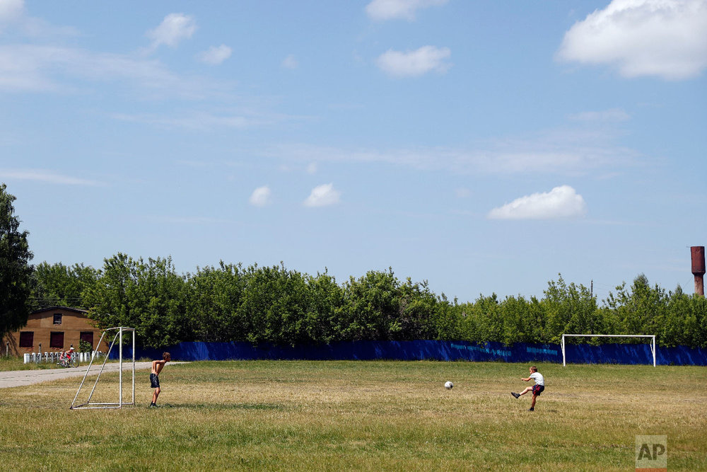 Children play with a ball in a soccer field in Kochkurovo village, outside Saransk, Russia on June 27, 2018. (AP Photo/Pavel Golovkin)