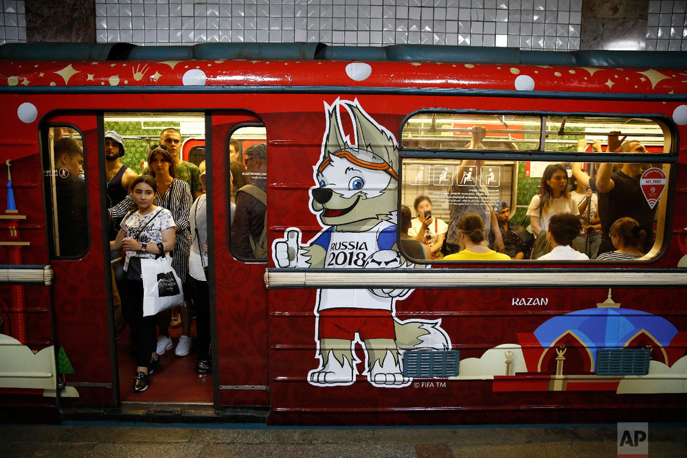 Commuters ride home on a subway car decorated for the 2018 soccer World Cup, in Moscow, Russia on June 30, 2018. (AP Photo/Rebecca Blackwell)
