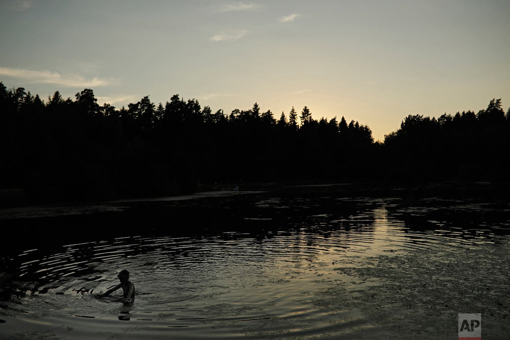 A youngster swims in a small forest lake at the 2018 soccer World Cup in Kratovo, outskirts Moscow, Russia on June 28, 2018. (AP Photo/Francisco Seco)
