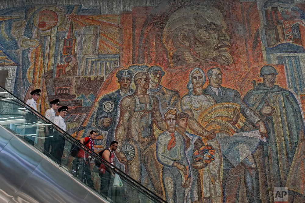 Soccer fans and police ride down an escalator at a subway station in front of a large soviet-era mural depicting Soviet founder Vladimir Lenin, top, during the 2018 soccer World Cup in Nizhny Novgorod, Russia on June 25, 2018. (AP Photo/Victor R. Caivano)