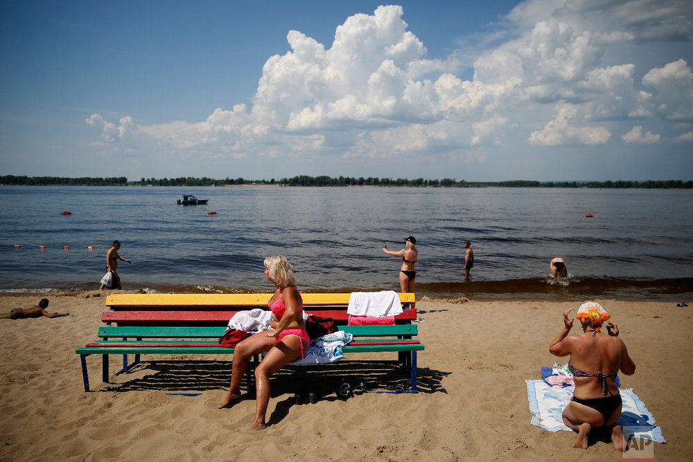 People spend a sunny day on a riverfront beach, during the 2018 soccer World Cup in Samara, Russia on June 26, 2018. (AP Photo/Rebecca Blackwell)