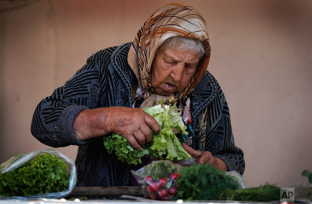 A woman prepares salad for sale on a local food market during the 2018 soccer World Cup in Kazan, Russia on June 29, 2018 (AP Photo/Frank Augstein)