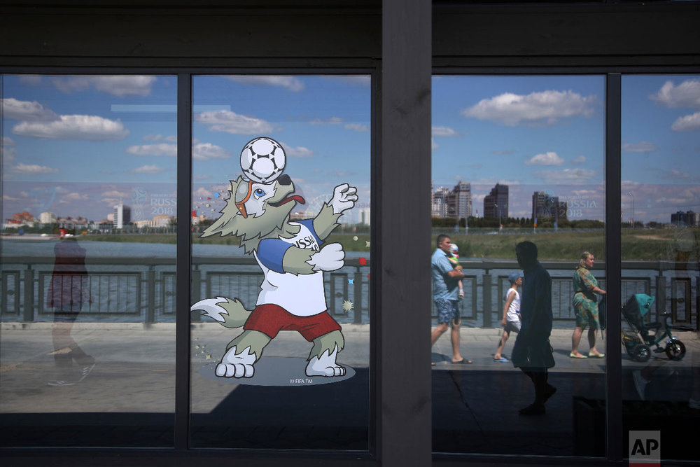 A volunteer, left, walks inside the Fan ID center as pedestrians are reflected in a window as they walk along the banks of the Volga river during the 2018 soccer World Cup in Kazan, Russia on June 29, 2018. (AP Photo/Thanassis Stavrakis)