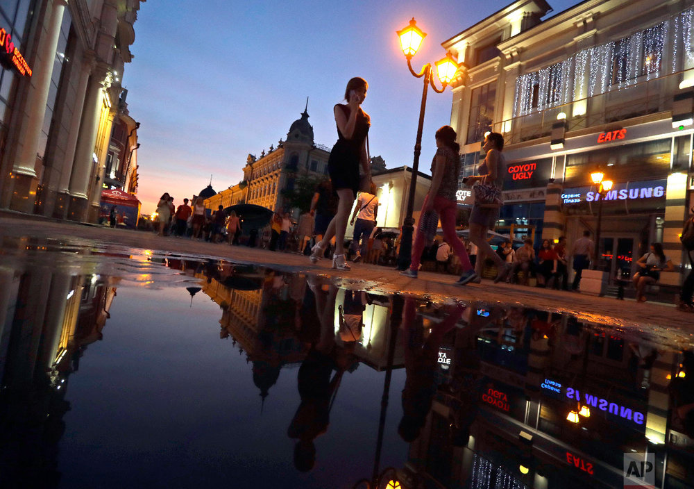 People walk at sunset during the 2018 soccer World Cup in downtown Kazan, Russia on June 26, 2018. (AP Photo/Sergei Grits)