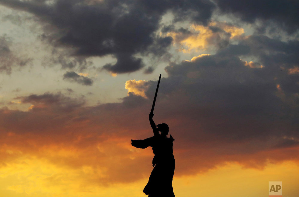 """The sun sets over """"The Motherland Calls"""" memorial during near the Volgograd Arena during the 2018 soccer World Cup in Volgograd, Russia on June 27, 2018. (AP Photo/Eugene Hoshiko)"""