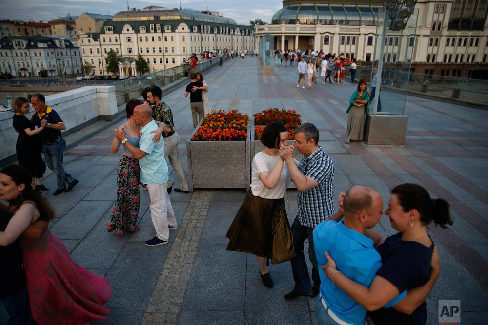 Couples dance the tango on Patriarshy Bridge during the 2018 soccer World Cup in Moscow, Russia on June 29, 2018. (AP Photo/Rebecca Blackwell)
