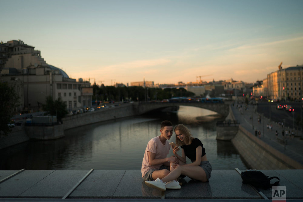 A young couple sit on a bridge as the sun sets during the 2018 soccer World Cup in Moscow, Russia on June 26, 2018. (AP Photo/Felipe Dana)