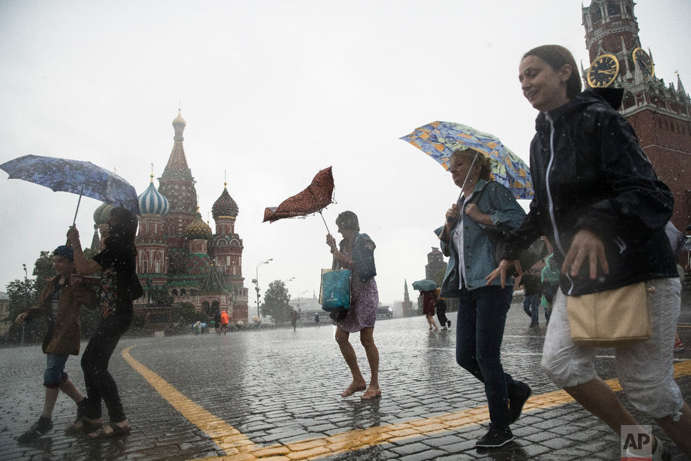 Tourists take cover from a heavy rain under umbrellas in Red Square with the with St. Basil's Cathedral, left, and the Spasskaya Tower, right, in the background, in Moscow, Russia on June 30, 2018. (AP Photo/Pavel Golovkin)