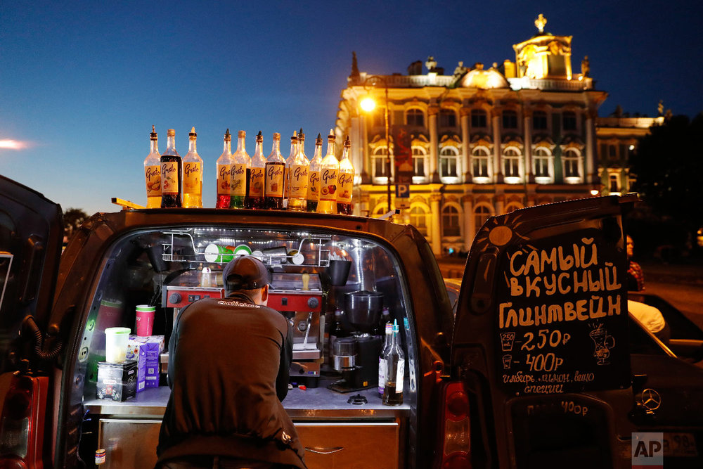 A vendor prepares coffee on the back of a van during the 2018 soccer World Cup in St. Petersburg, Russia on June 26, 2018. (AP Photo/Ricardo Mazalan)