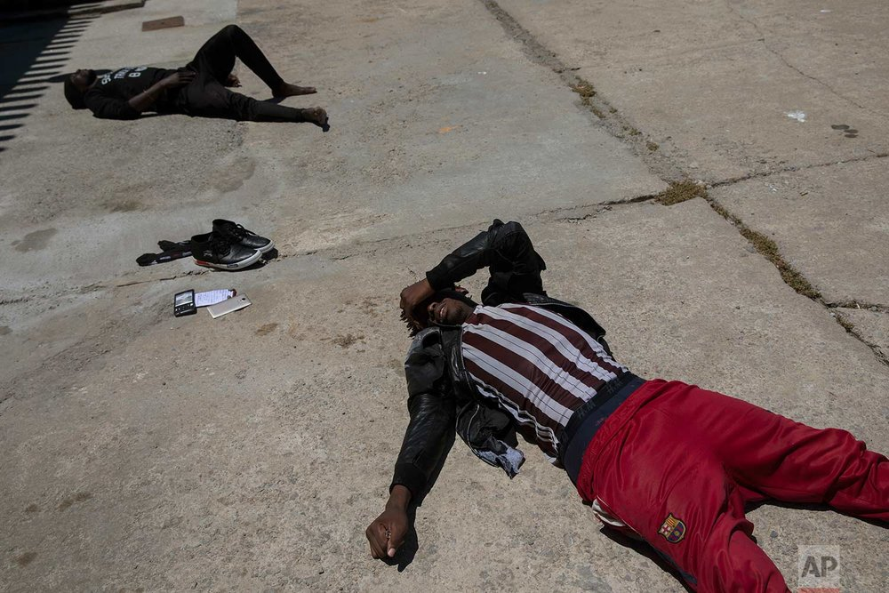 Migrants lay on the ground exhausted at the port of Tarifa, southern Spain, after being rescued by Spain's Maritime Rescue Service in the Strait of Gibraltar, Friday, June. 29, 2018. European Union leaders declared victory Friday, claiming to have set aside major differences over how best to handle migrant arrivals as they commissioned new plans to screen people in North Africa for eligibility to enter Europe. (AP Photo/Emilio Morenatti)