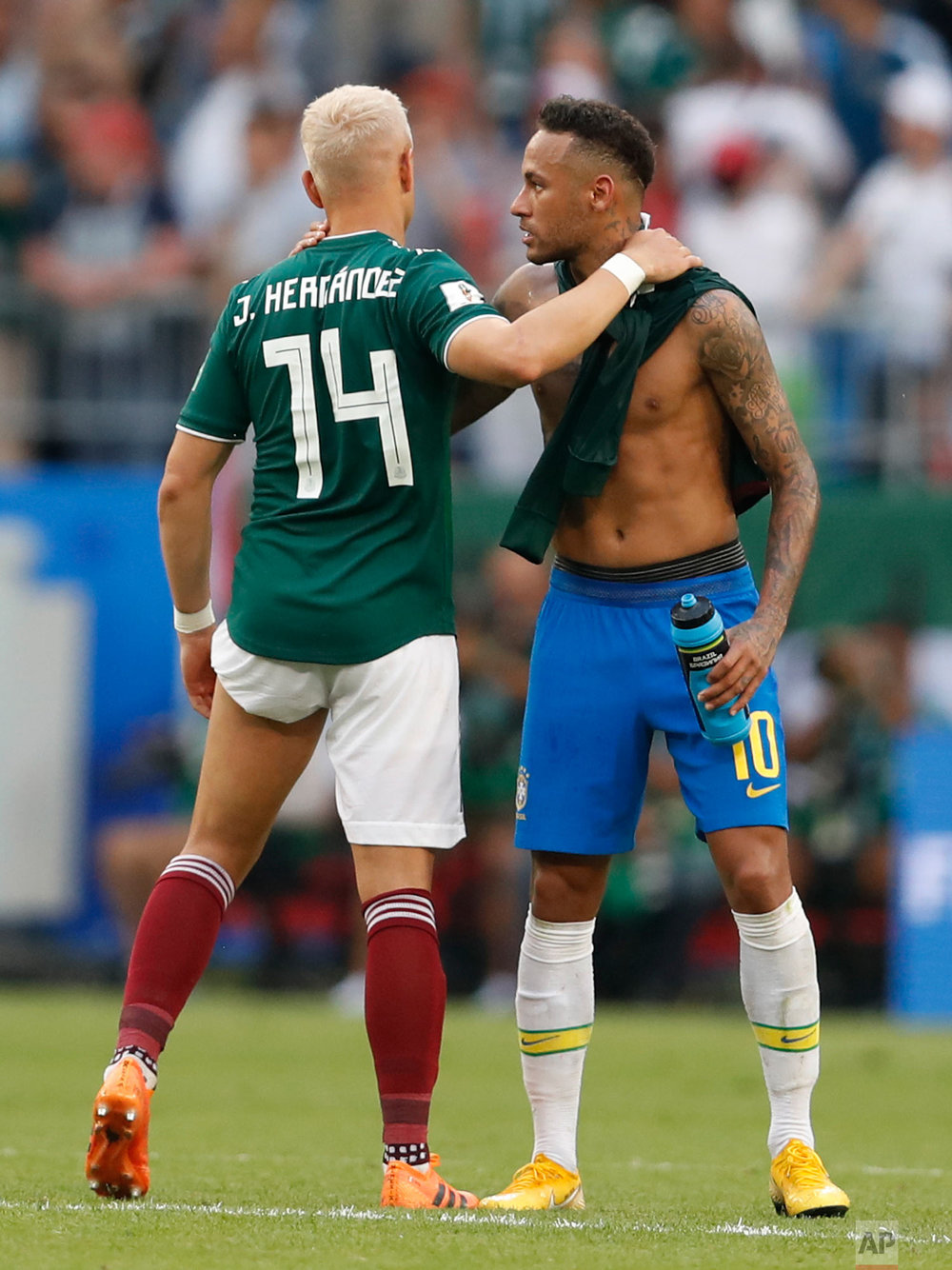 Mexico's Javier Hernandez (14) embraces Brazil's Neymar after their round of 16 match at the 2018 soccer World Cup in the Samara Arena, in Samara, Russia, Monday, July 2, 2018. Brazil won 2-0. (AP Photo/Eduardo Verdugo)