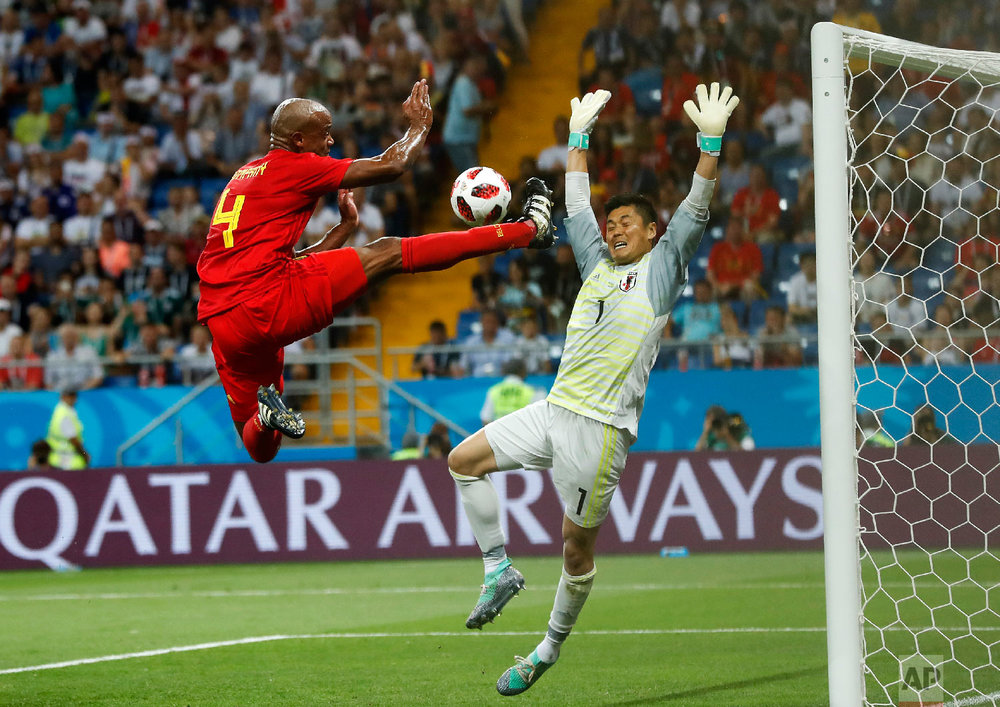 Belgium's Vincent Kompany jumps for the ball in front of Japan goalkeeper Eiji Kawashima during the round of 16 match between Belgium and Japan at the 2018 soccer World Cup in the Rostov Arena, in Rostov-on-Don, Russia, Monday, July 2, 2018. (AP Photo/Petr David Josek)