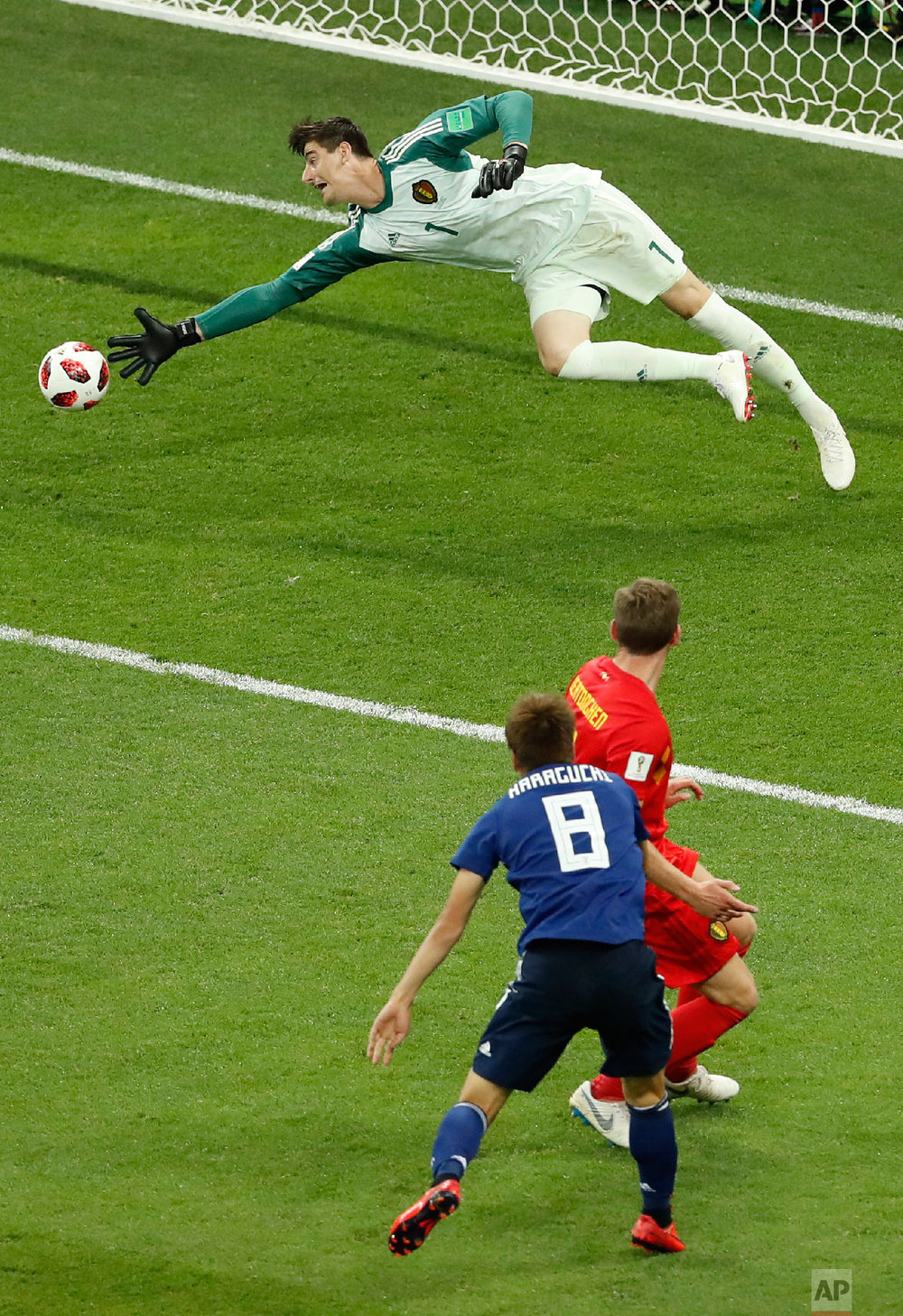 Japan's Genki Haraguchi, bottom left, scores his first side goal during the round of 16 match between Belgium and Japan at the 2018 soccer World Cup in the Rostov Arena, in Rostov-on-Don, Russia, Monday, July 2, 2018. (AP Photo/Hassan Ammar)